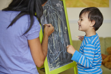 Mum and boy drawing on blackboard