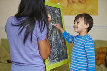 Mum and boy drawing on blackboard