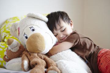 Boy cuddling a teddy