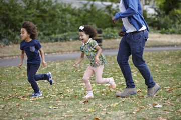 Children with dad running in the park