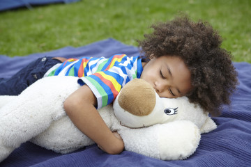 Boy snoozes with teddy