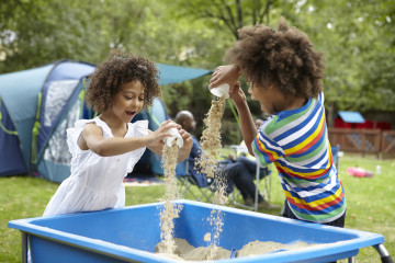 Siblings playing in sand pit