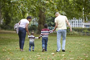 Mum, Dad and children walking in park