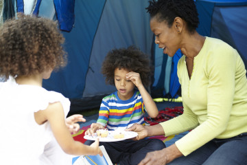 Mum, son and daughter picnic outside tent