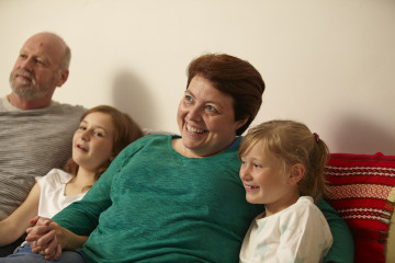 Mum, dad and daughters watching TV