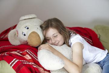 Girl snoozing with teddy bear