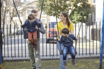 Mum and Dad pushing children on swings
