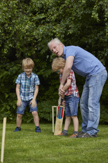 Dad and children playing cricket
