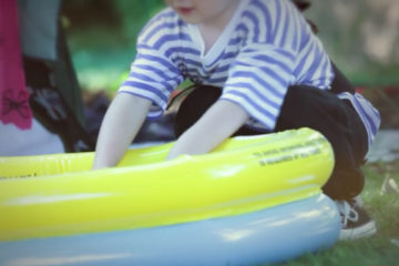 Boy dressed as pirate next to paddling pool at Adoption Activity Day