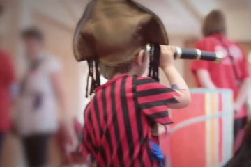 Boy dressed as pirate with telescope at Adoption Activity Day